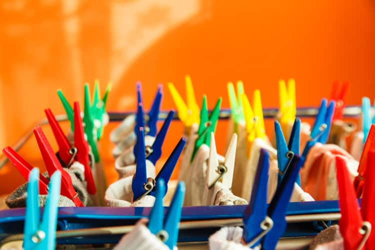 Housework concept. Closeup clothes hanging to dry on a laundry line with colorful pegs clips indoor