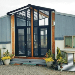 Two Tiny Homes Connected By a Central Sunroom